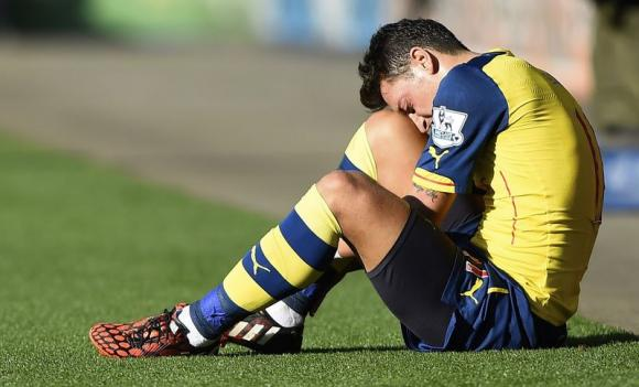 Arsenal's Mesut Ozil sits injured during their English Premier League soccer match against Leicester City at the King Power Stadium in Leicester