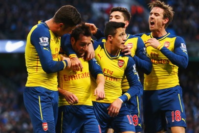 Man of the Match Santi Cazorla is mobbed by his team mates